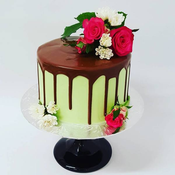 Smooth Green Cake with Chocolate Drip and Fresh Flowers