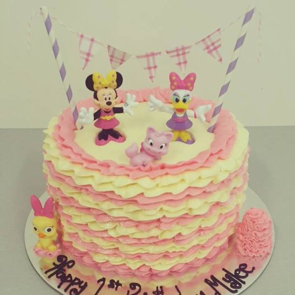 Cream and Pink Ruffle Cake with Minnie Mouse Figurines and Bunting
